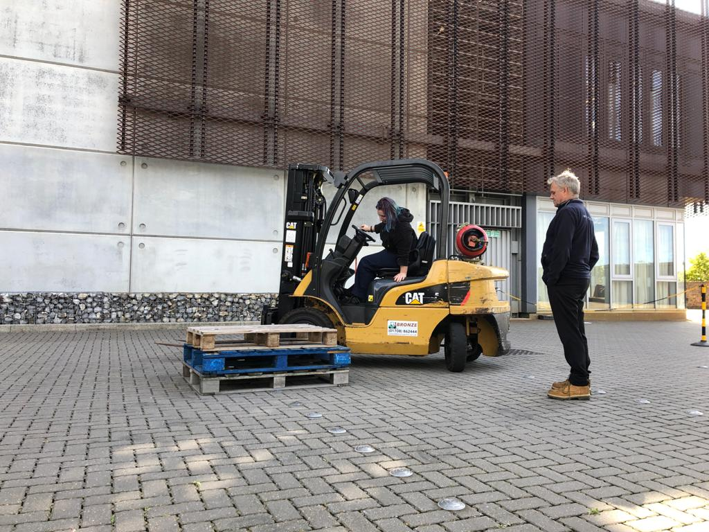 Phoebe driving a yellow forklift truck, there are wooden pallets in the foreground.  An assessor stands to the right f the truck watching her drive